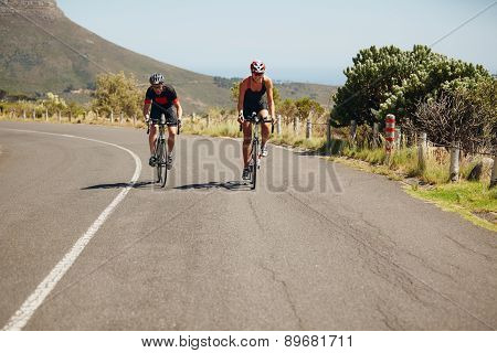 Cyclist riding bikes on open road. Triathletes cycling on bicycles. Practicing for triathlon race. poster