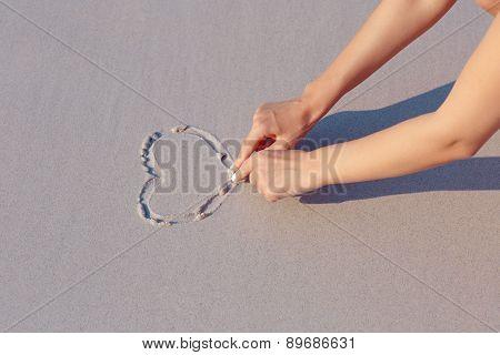 Drawing on beach sand heart symbol