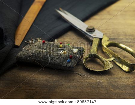 Gold scissors pin cushion, and black fabric.Measuring, cutting, sewing textile or fine cloth. Work table of a tailor. Shallow depth of field, Focus in on  pin on the pin cushion.