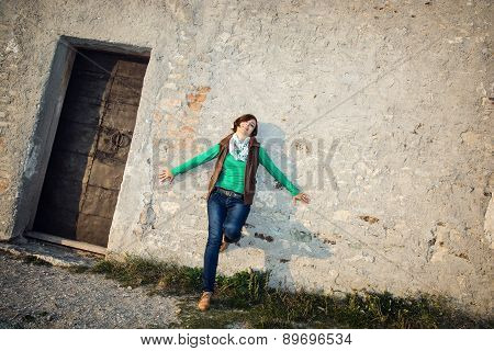 Young Woman Posing In Front Of The Old Wall
