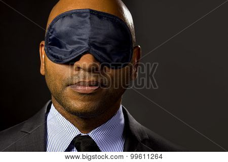 Sleepy businessman wearing an eye mask.  He may be sleepy from business travel or insomnia. poster