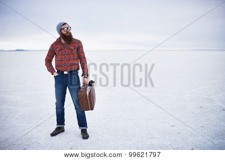 totally unconcerned lone traveling hipster standing with retro suitcase in vast empty salt flats with copy space composition