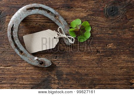 St.Patricks day, lucky charms. Four leaved clover and a horseshoe on wooden board