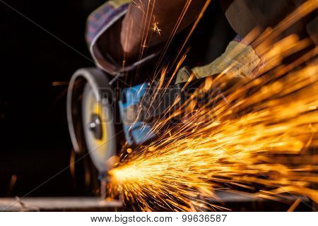 Close-up of worker cutting metal with grinder. Sparks while grinding iron. Low depth of focus poster