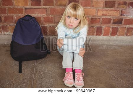Portrait of sad pupil sitting alone on ground at corridor