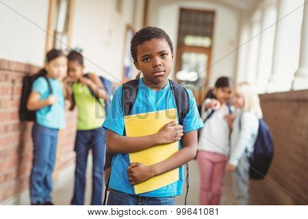 Portrait of sad pupil being bullied by classmates at corridor in school poster