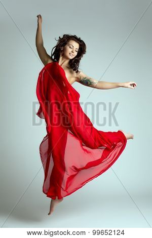 Graceful female dancer posing in jump. Studio photo poster