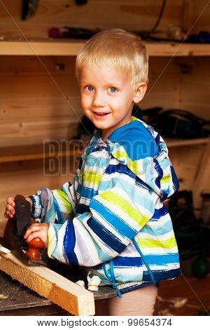 cutest boy in the workshop of a carpenter planed wood