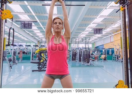 Portrait of beautiful woman stretching her arms in a sport bar before to start a crossfit training on fitness center poster