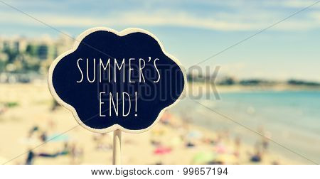 closeup of a chalkboard in the shape of a thought bubble with the text summers end written in it, with a blurred beach in the background, filtered