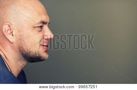 Profile portrait of bald man with copyspace.  poster