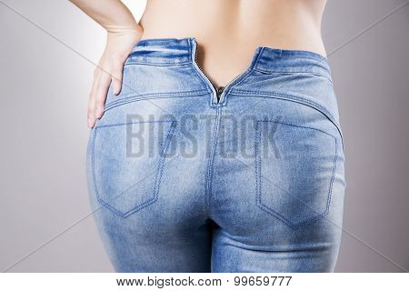 Woman in jeans close up. Beautiful female hips and buttocks on a gray background poster