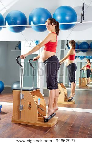 pregnant woman pilates tendon stretch exercise in wunda chair at gym indoor