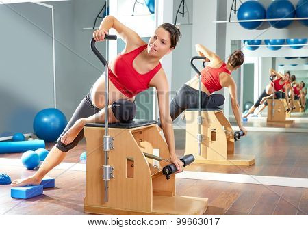 pregnant woman pilates side stretch exercise on wunda chair at gym indoor