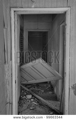 Abandoned house hallway with unhinged door and rubble on dirty floor. Black and white. poster