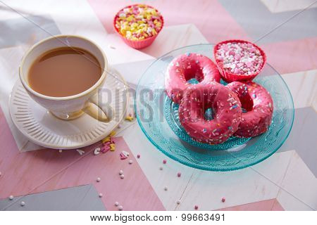 Tea with milk breakfast with pink donas and cupcake topings