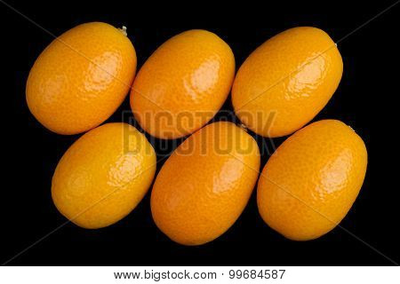 Oblique oval kumquats closeup. Macro photo from above on black background. poster