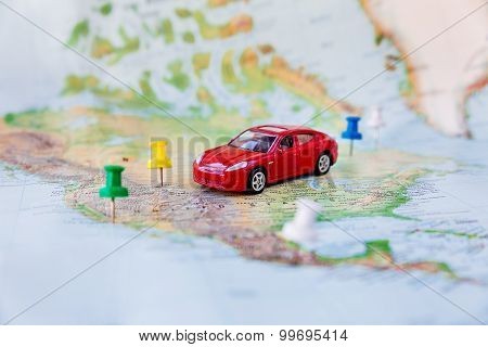 Road Trip - Car Goes On Map Across The Territory Of The Usa. The Route Of Automobile Travel.
