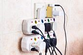 Multiple electricity plugs on adapter risk overloading and dangerous. poster