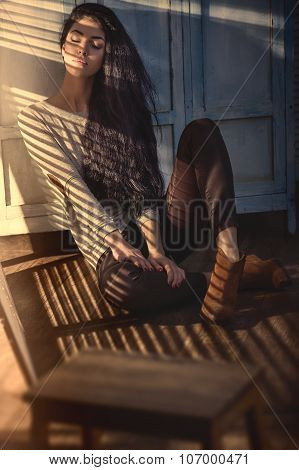 Beautiful brunette with chic long hair sitting in the setting su