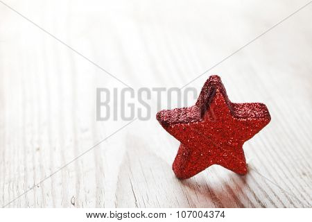 Red Christmas star on wooden background macro close-up