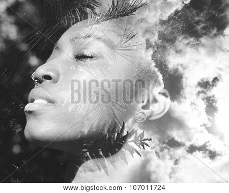 Double exposure portrait of african american woman combined with photograph of trees and sky