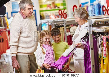 Grandmother showing new tanktop for granddaughter in the mall
