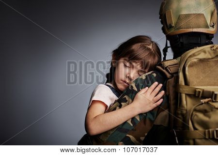 Sleeping child held by warrior in camouflage