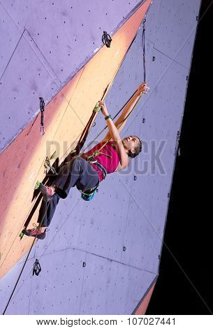 Female extreme climber fixing the rope into belay quick draw