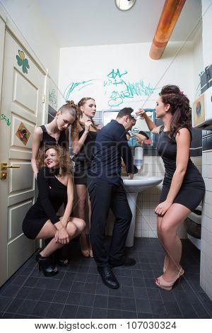 man in toilet with drunk women