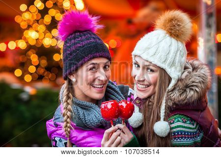Women eating crystalized apples on German Christmas Market