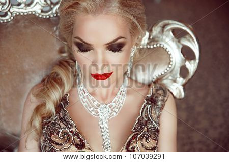 Fashion Indoor Portrait Of Beautiful Sensual Blond Woman With Makeup In Luxurious Dress With Bijou,