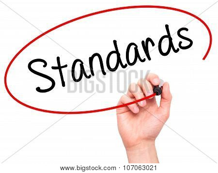 Man Hand writing Standards with black marker on visual screen.