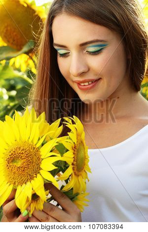Bea?tiful girl in the sunflowers field