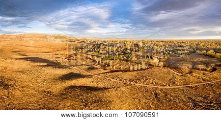 aerial panorama of foothills prairie and residential areas along Front Range of Rocky Mountains near Fort Collins, Colorado, fall scenery lit by sunrise