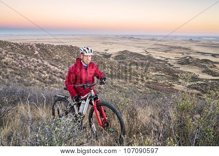 senior male with a mountain bike in a rolling prairie at dusk, Soapstone Prairie Natural Area near Fort Collins, Colorado