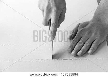 Man cuts with a knife polystyrene