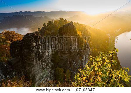 View into deep misty valley in Saxon Switzerland. Sandstone peaks increased from foggy background, the fog is orange due to sunrise. Bastei Bridge. Soft Focus on tree
