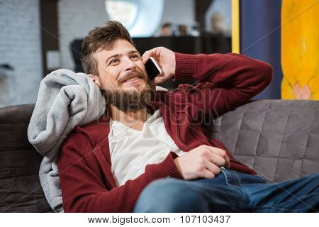 Smiling happy handsome boy with beard in brown hoodie lying on grey sofa and talking on mobile phone