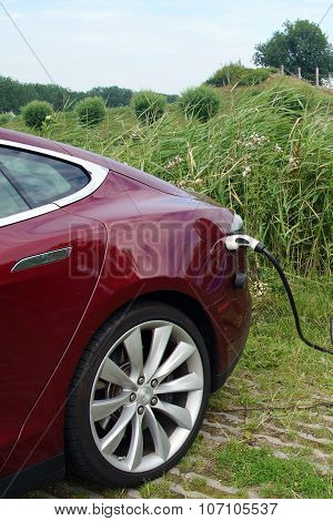 Red Tesla Model S being charged - vertical