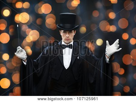 performance, circus, show concept - magician in top hat and cape showing trick with magic wand over nigh lights background