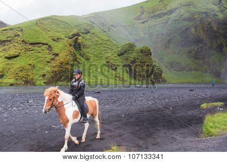 Skogafoss waterfall with horses and jockeys. Iceland