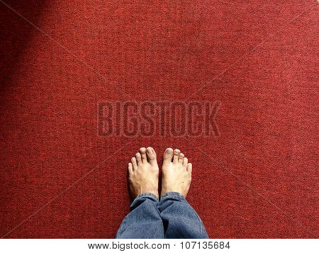 Pair of feet on a red carpet