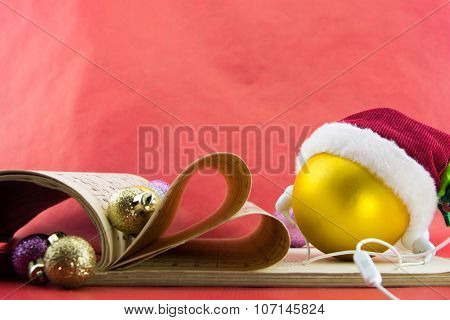Christmas Ball With Santa's Hat And Earphones, Music Notation Book With Pages Shaping Heart, On Red