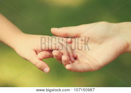 Mother's hand lead her child daughter outdoors on green defocused background, trust family concept