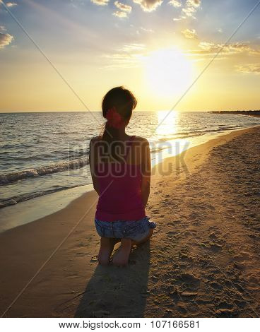 Girl Kneeling On The Beach