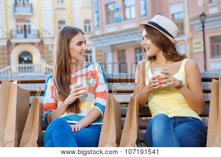 Two friends relaxing on the bench during shopping