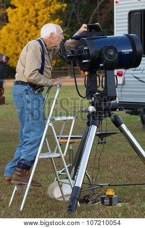 Senior Astronomy Hobbyist Aligns Telescope