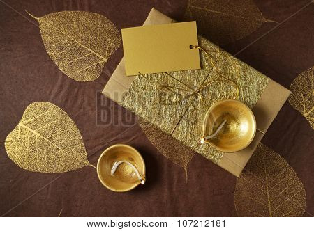 Glittering golden gift box with a blank tag and Indian traditional lamps. Diwali festive gift background. View from top.
