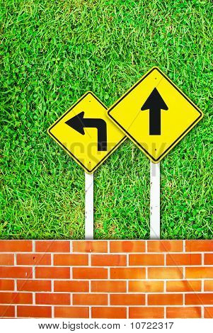 Traffic Sign On Brick Wall And Grass Field